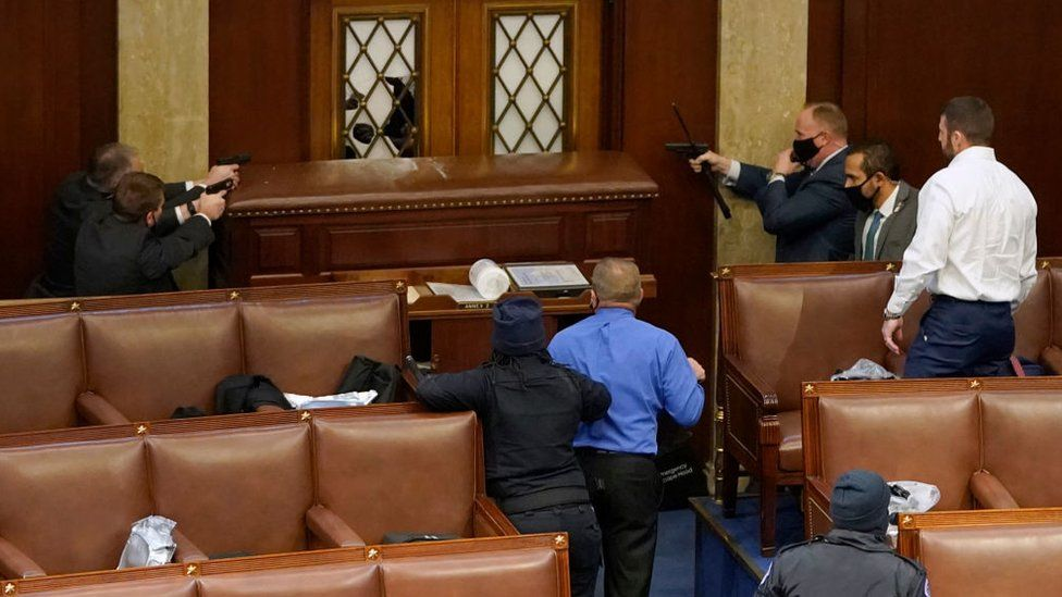 Capitol police officers point guns at a protester from inside the Senate chamber; Photo: Getty Images